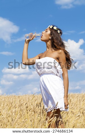 Young beautiful woman quenches thirst in a wheat golden field - stock photo