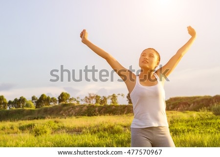 Young beautiful woman raised arms enjoying the fresh air in green meadows.