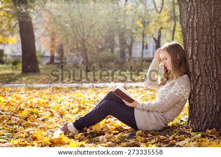 Young beautiful woman reading a book at the park - stock photo