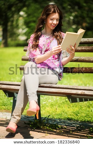 Young Beautiful Woman Reading Book In The Park, and sitting on the Park Bench. - stock photo