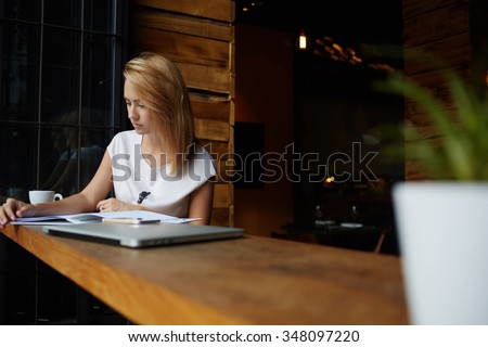 Young beautiful woman reading magazine during coffee break in cafe, charming female student preparing for lectures while sitting in bar, attractive hipster girl relaxing in restaurant during lunch  - stock photo