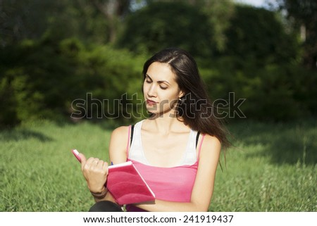 Young beautiful woman reading outdoors