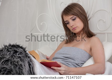 Young beautiful woman reads book in bedroom.