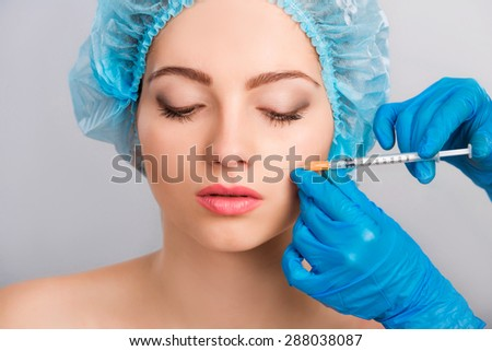 Young beautiful  woman receiving a cosmetic botox injection in her face, close up