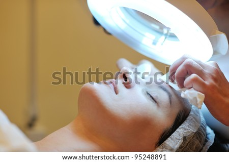 Young beautiful woman receiving cosmetic facial mask in spa beauty salon and relax - stock photo
