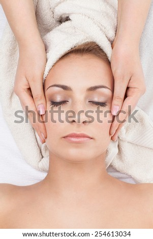 Young beautiful woman receiving face massage in spa salon - stock photo