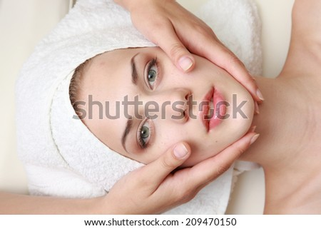 Young beautiful woman receiving facial massage and spa treatment - stock photo