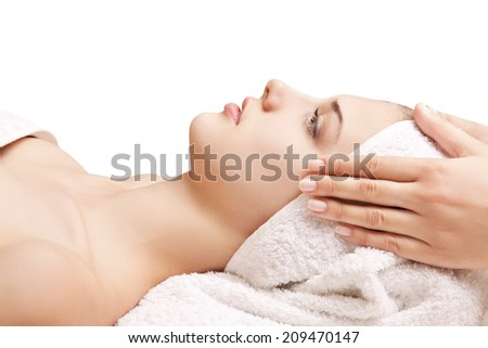 Young beautiful woman receiving head massage and spa treatment