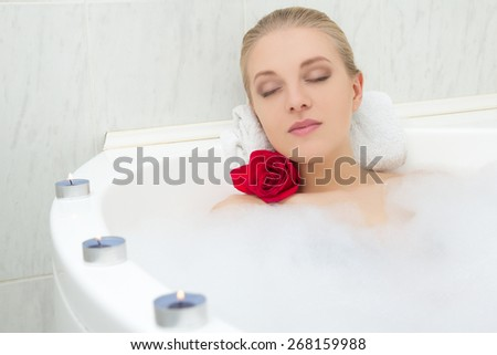 young beautiful woman relaxing in bath with flower and candles - stock photo