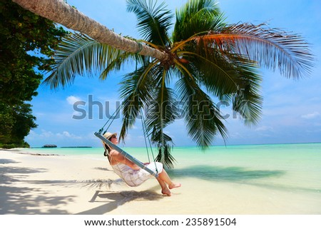 Young beautiful woman relaxing in swing hanging on coconut palm at tropical beach - stock photo