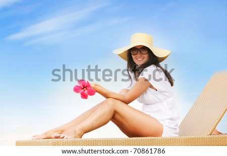 young beautiful woman relaxing isolated on sky background