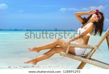 young beautiful woman relaxing on sand beach