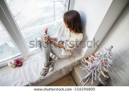 Young beautiful woman relaxing with hot coffee on window sill in christmas decorated home. Top view