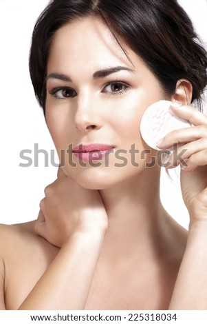 young beautiful woman remove makeup from perfect skin on white - stock photo