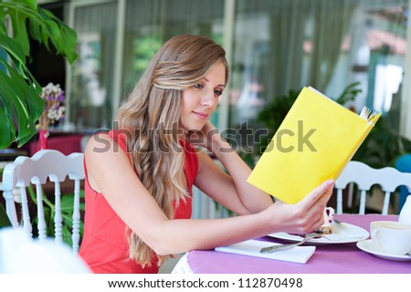 young beautiful woman resting in cafe and reading the book - stock photo