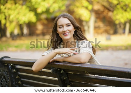 Young beautiful woman resting on a bench in the autumn park - stock photo