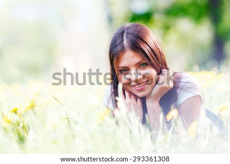 Young beautiful woman resting on fresh green grass with flowers