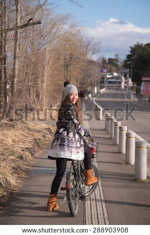 Young beautiful woman riding a bicycle at kawaguchiko Lake,Japan. Active people. Outdoors - stock photo