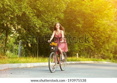 young beautiful woman riding a bicycle in a park. Active people. Outdoors - stock photo