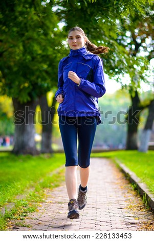 Young Beautiful Woman Running in the Autumn Park. Active Lifestyle