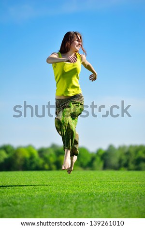 Young beautiful woman running on a green meadow