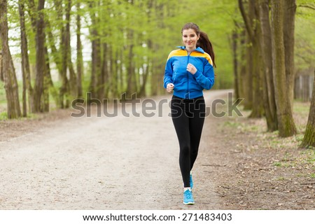 Young beautiful woman running on a trail.