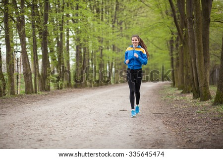 Young beautiful woman running on a trail. - stock photo