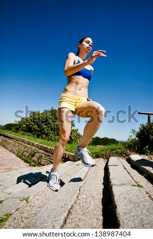 Young beautiful woman running upstairs on a summer day - stock photo