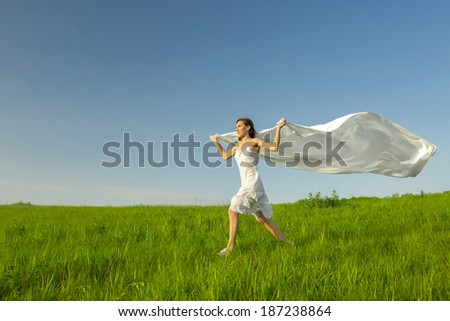 Young beautiful woman running while holding a white tissue