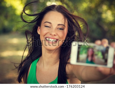 Young beautiful woman shooting self portrait - stock photo