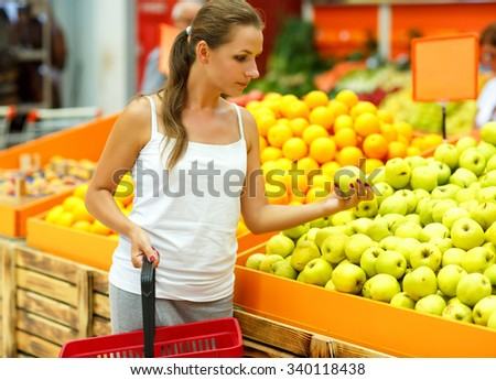 Young beautiful woman shopping in a supermarket in the department of fruit and vegetables