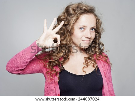 Young beautiful woman showing hand ok sign