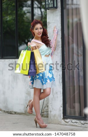 Young beautiful woman shows an ecstatic expression while holding shopping bags outside shopping mall.