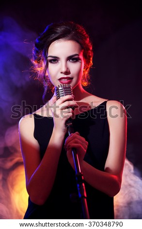 Young beautiful woman singing in colourful smoke, close up - stock photo