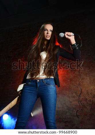 Young beautiful woman singing on the scene - stock photo