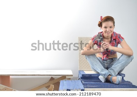 Young beautiful woman sits and thinks of repair - stock photo