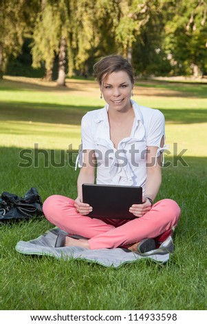Young, beautiful woman sits on a meadow with a laptop