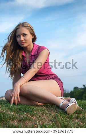 Young beautiful woman sits on grass in summer day