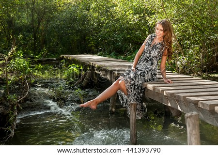 Young beautiful woman sits on wooden bridge and plays with water