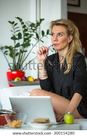 Young beautiful woman sits pensively with a laptop. - stock photo
