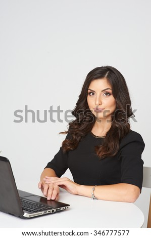 Young beautiful woman sitting at a desk in the office. next to her laptop. Her dark long hair, white teeth, she smiles.