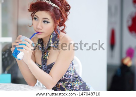 Young beautiful woman sitting at outdoor cafe holding soft drink glass, Model is Thai Ethnicity. - stock photo