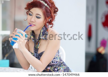Young beautiful woman sitting at outdoor cafe holding soft drink glass, Model is Thai Ethnicity.