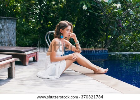 young beautiful woman sitting at pool in white tropical dress, sunny summer day, happy  mood, fashion trend accessories, thinking, dreaming, romantic travel, vacation on island, resort, honey moon - stock photo