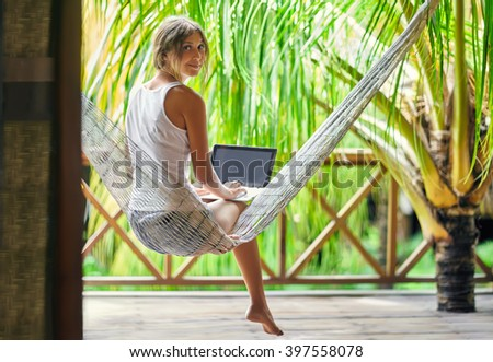 Young beautiful woman sitting in a hammock with laptop in a tropical resort. back view. - stock photo