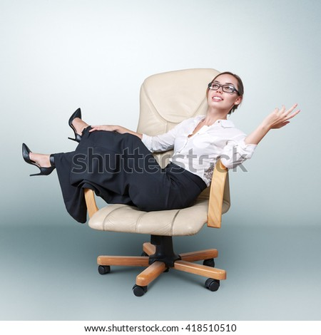 Young beautiful woman sitting in armchair studio portrait