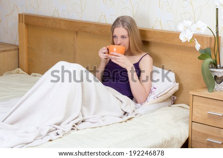 young beautiful woman sitting in bed with mug of coffee or tea - stock photo