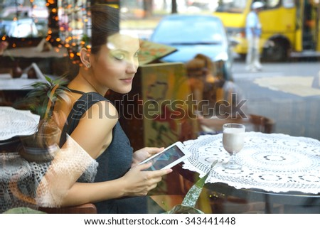 Young beautiful woman sitting in cafe, drinking coffee and using her smartphone. Image toned, noise added. - stock photo