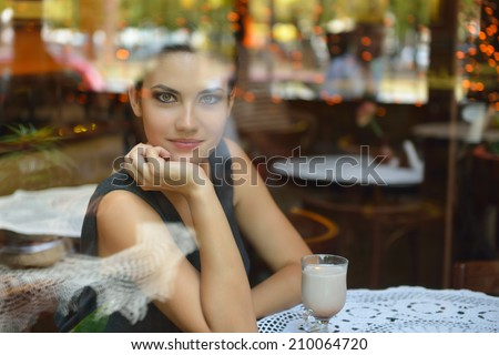 Young beautiful woman sitting in cafe, drinking coffee. Image toned, noise added. - stock photo