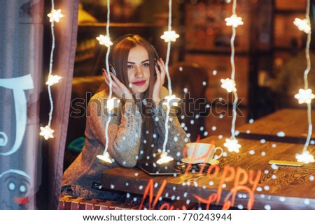 Young beautiful woman sitting in cafe, drinking coffee. Model listening to music. Magic snowfall effect. Christmas, new year, Valentines day, winter holidays concept.
